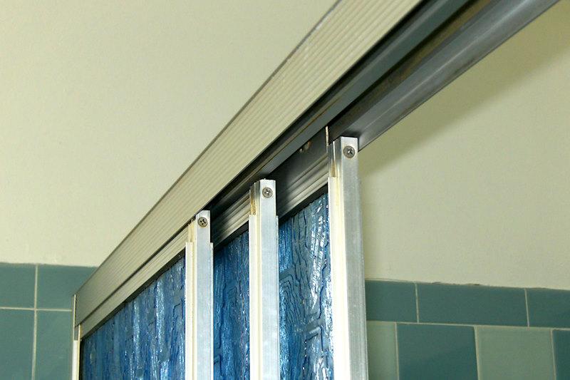 A retro renovation, save the bue bathroom. Sliding glass shower doors.